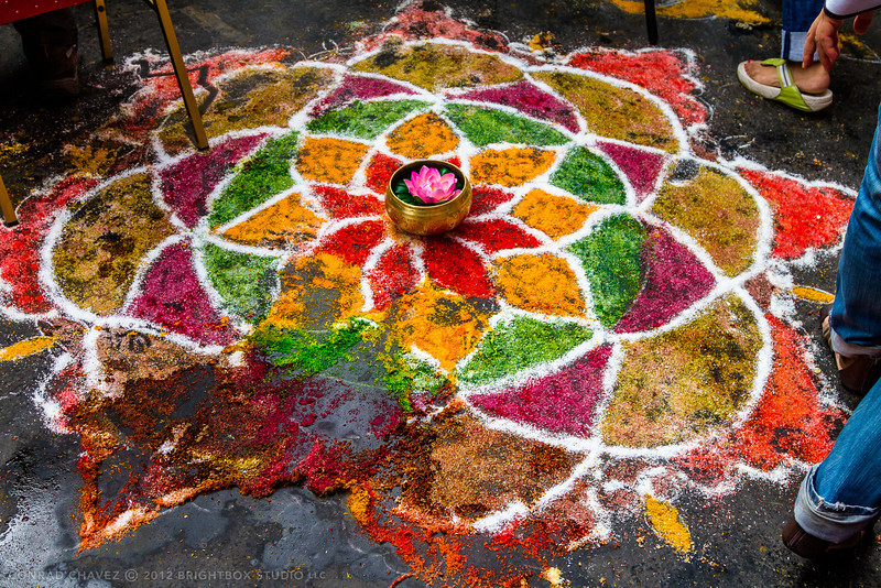 The packed crowds mostly manage to avoid trampling rangoli artwork created on the street.