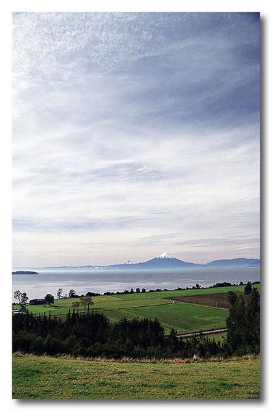Green meadows, volcano Osorno and lake Llanquihue. Puerto Varas, Chile.