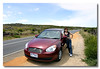 Wife with our rented car at Great Ocean Road. Victoria.