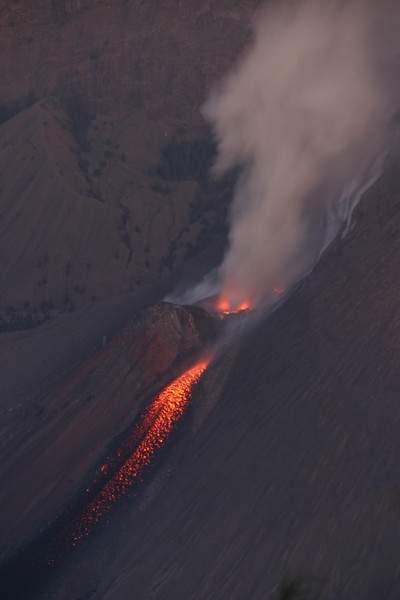 When it got dark, it became easier to see the lava flowing down Mount Barujari.  Mount Barujari is a cone in the middle of the caldera. Mount Rinjani, Lombok, Indonesia.