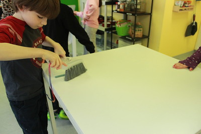 a boy cleaning a table