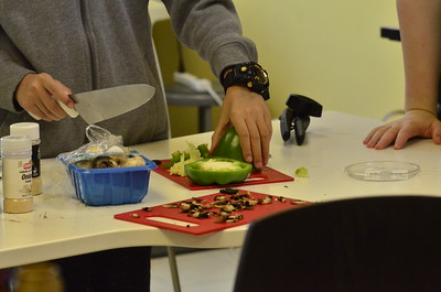 a person with a knife cutting  peppers in culinary