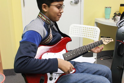 Kristchov playing the electric guitar in rock band class.