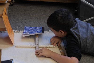 nathan doing a lever work whith a pvc pipe , ruler , book , and instoction card in upper el room