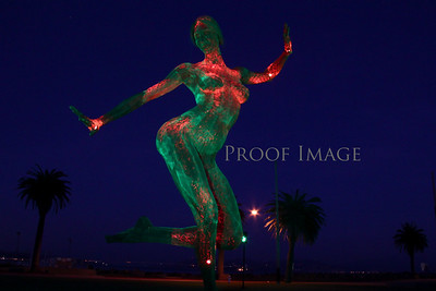 A naked woman standing on one foot as she dances, hands in the air, lit by 1,000 LED lights.