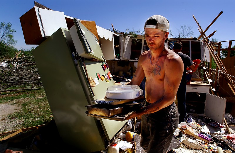 00b0xjbltornado07.cut JESSICA BRANDI LIFLAND / Courier & Press James Baker carries some pots and pans out of the kitchen of his friends Joe and Melissa Morrow's mobile home at the West Side Mobile Home Park on Tower Drive on Baptist Hill in Providence, Kentucky on Sunday afternoon after a tornado destroyed much of the park early Sunday morning.