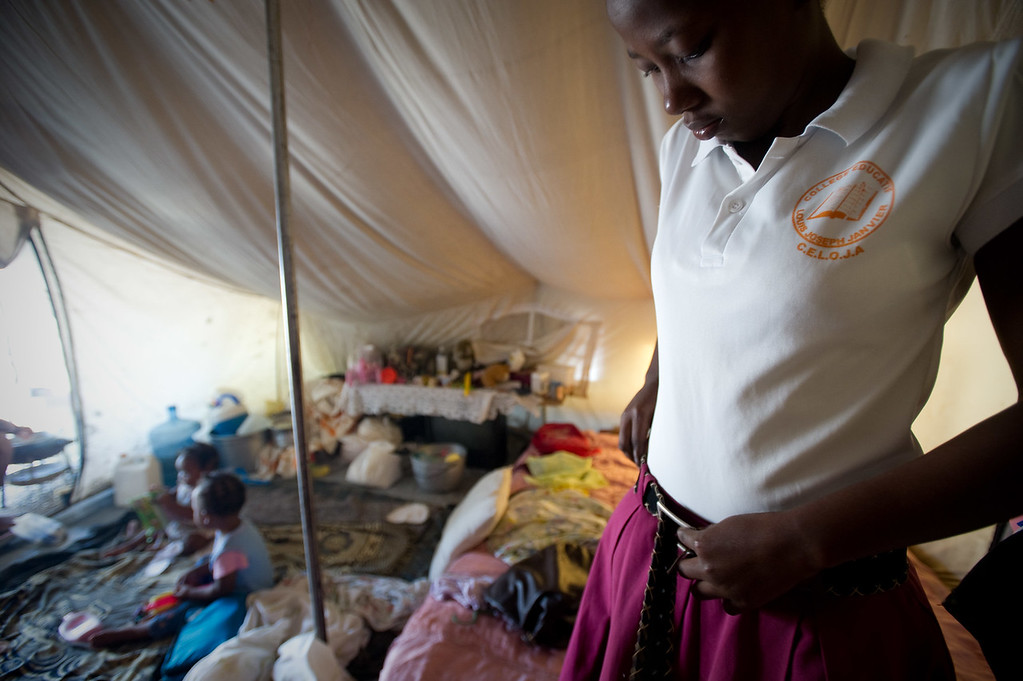 """Port Au Prince, Haiti.  Wednesday, June 30, 2010.<br /> <br /> //Anide Fleureme has a drink of water while studying in her family's tent. Anide, 24, is a school girl attempting to graduate from 12th grade at Ecole Centre Educatif-Luis Josephe Jamlien this year. Anide was in the school during the earthquake but managed to escape. The school is now reopened under a tent just a few lots away from the original building location. <br /> <br /> Anides says likes accounting and hopes that when she finished high school she could go to college, but she says """"The country is broken right now so I don't know what will happen."""" <br /> <br /> Anide lives with her 2 cousins, 3 nieces and a nephew in a tent in a camp in the Delmas neighborhood of Port au Prince. Haiti.  They used to live in a one bedroom home with a livingroom, but it was cracked beyond repair in the earthquake so now they are IDP (Internally displaced people.) //"""