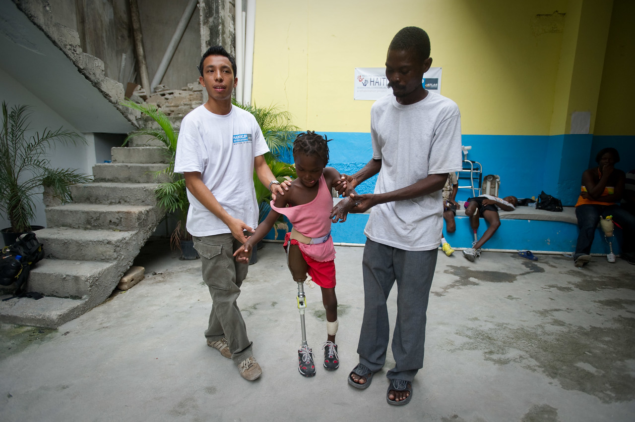 Port Au Prince, Haiti.  Wednesday, June 30, 2010.  //Mirlanda Pierre, 12, is fitted for a Prosthetic leg at Handicap International in Port Au Prince, Haiti. At left s her father Mirto Pierre and at right is Alex from El Salvador. Mirlanda was pulled from the rubble of a neighbor's house three days after the earthquake. She and her father have been at MSF  (Medicine Sans Frontiers) field hospital in Delmas 31 ever since as she sustained injuries which included the loss of her leg and the loss of use of her left hand.  She is one of many residents of Port Au Prince receiving aid for injuries at Handicap International, which has had a presence in Haiti since before the earthquake but has stepped up its presence considerable in the wake of the earthquake. Many of its patients who have lost limbs are healing up to the point where they can be fitted for more permanent prosthetics. Port Au Prince, Haiti, //