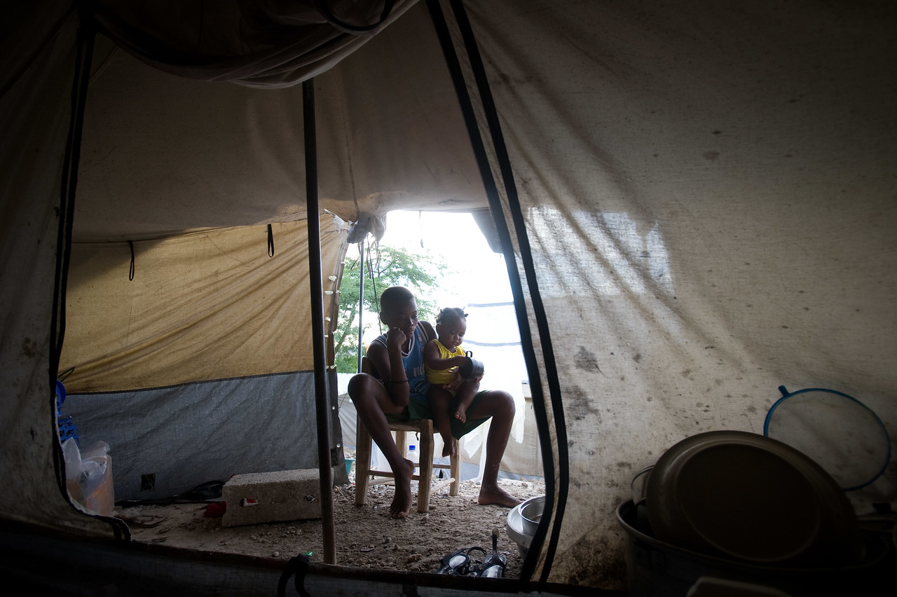 """Haiti.  Monday, June 28, 2010.  //Anide Fleureme has a drink of water while studying in her family's tent. Anide, 24, is a school girl attempting to graduate from 12th grade at Ecole Centre Educatif-Luis Josephe Jamlien this year. Anide was in the school during the earthquake but managed to escape. The school is now reopened under a tent just a few lots away from the original building location.   Anides says likes accounting and hopes that when she finished high school she could go to college, but she says """"The country is broken right now so I don't know what will happen.""""   Anide lives with her 2 cousins, 3 nieces and a nephew in a tent in a camp in the Delmas neighborhood of Port au Prince. Haiti.  They used to live in a one bedroom home with a livingroom, but it was cracked beyond repair in the earthquake so now they are IDP (Internally displaced people.) //"""