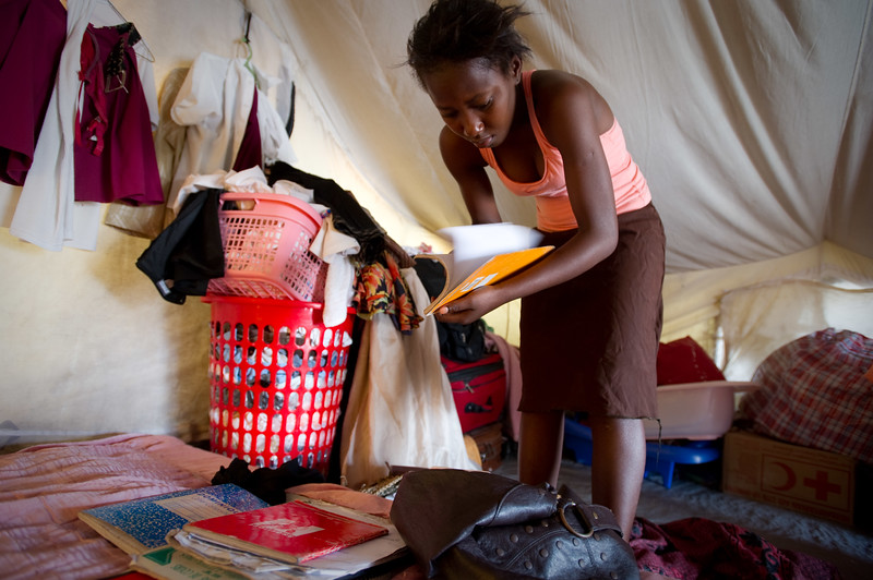 """Port Au Prince, Haiti.  Wednesday, June 30, 2010.  //Anide Fleureme has a drink of water while studying in her family's tent. Anide, 24, is a school girl attempting to graduate from 12th grade at Ecole Centre Educatif-Luis Josephe Jamlien this year. Anide was in the school during the earthquake but managed to escape. The school is now reopened under a tent just a few lots away from the original building location.   Anides says likes accounting and hopes that when she finished high school she could go to college, but she says """"The country is broken right now so I don't know what will happen.""""   Anide lives with her 2 cousins, 3 nieces and a nephew in a tent in a camp in the Delmas neighborhood of Port au Prince. Haiti.  They used to live in a one bedroom home with a livingroom, but it was cracked beyond repair in the earthquake so now they are IDP (Internally displaced people.) //"""