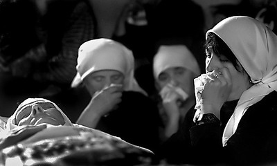 Albanian women gather in a farmhouse for the funeral of woman who was said to be over 100 years old.The sister-in-law of the deceased, Lathe Muriqui said the woman had been grateful to be dying at home surrounded by friends and family rather than as a refugee abroad.
