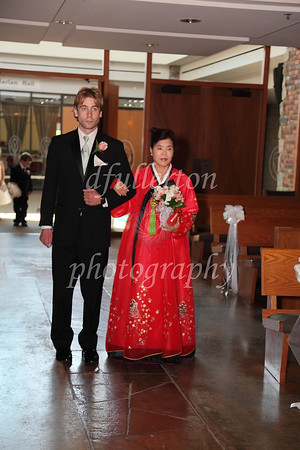 Ahra's mother being escorted down the aisle.
