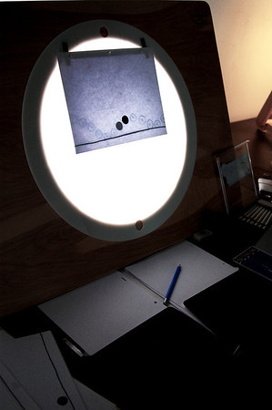 Jan 26th The animators work space. Tools of the trade; blank paper, finished drawings, drawing tools and a light box.