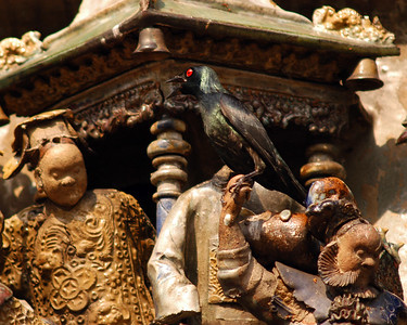 Statue façade of a temple, Kuala Lumpur. That is a real bird on the hand of the statue.