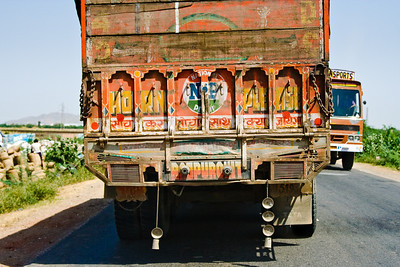 Many trucks hang vehicle parts as ornamentation, decorating them like elephants. National Highway 8, Rajasthan, India  |  2007