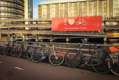 All of the common elements of cycling in Amsterdam: the red bike lane, bikes locked to canal rails, the enormous bike ramp in the background. Amsterdam Loves Bicycling.