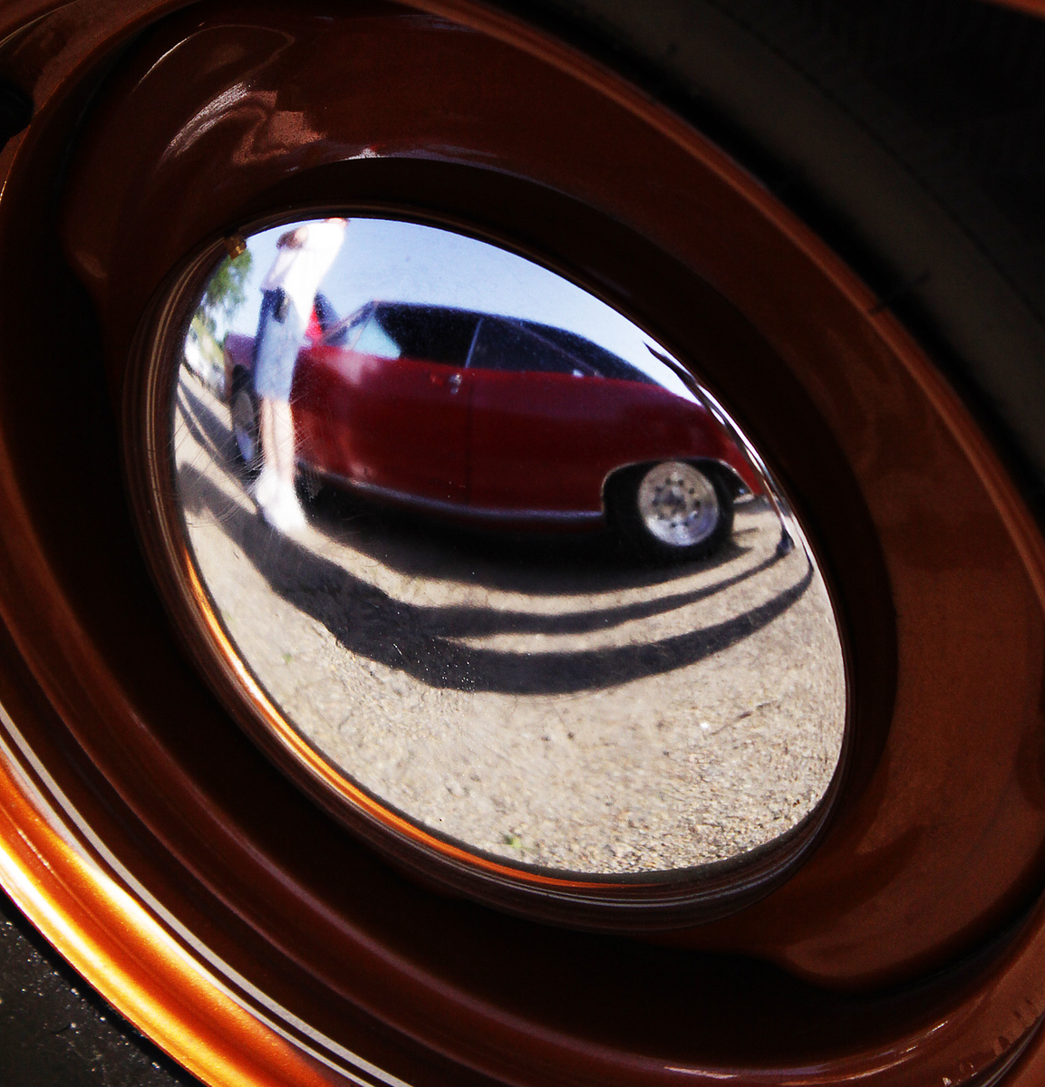 A dodge duster is seen in the reflection of a Ford Fairlane hubcap.