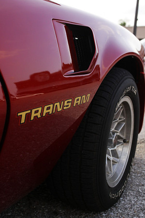 The right front fender clearly reveals the work of a 1979 Pontiac T/A. This beautiful red car is a rare convertible, and shows why Trans-Ams were an icon for decades.
