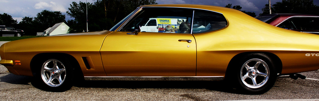A very gold 1972 Pontiac GTO with aftermarket rims.