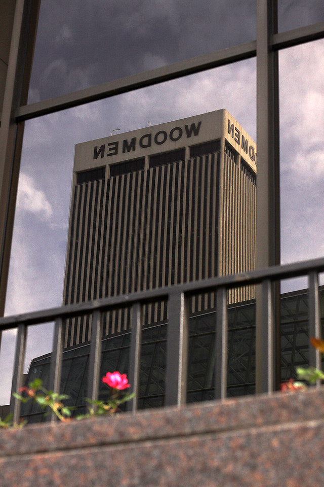 The second-tallest building in Nebraska, the Woodmen Tower, caught in the reflection of a window of the old First National building across the street from the First National Tower.