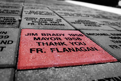 Memorial bricks from various donors surrounding the statue of Father Flannigan in Omaha, Nebraska.