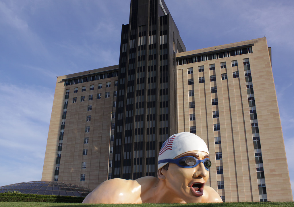 This statue sits in front of Mutual of Omaha's headquarters building on 33rd and Dodge Streets in Omaha, Nebraska. Mutual is a sponsor of the Olympic swimming trials. Despite its likeness, Mutual of Omaha officials state the likeness of the statue is not Michael Phelps, who the company stopped sponsoring following his publicized marijuana smoking from several years ago.