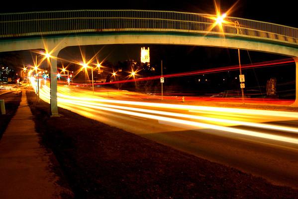 Street view of traffic streaming on Dodge Street passing underneath the Memorial Park bridge in the Dundee neighborhood of Omaha.