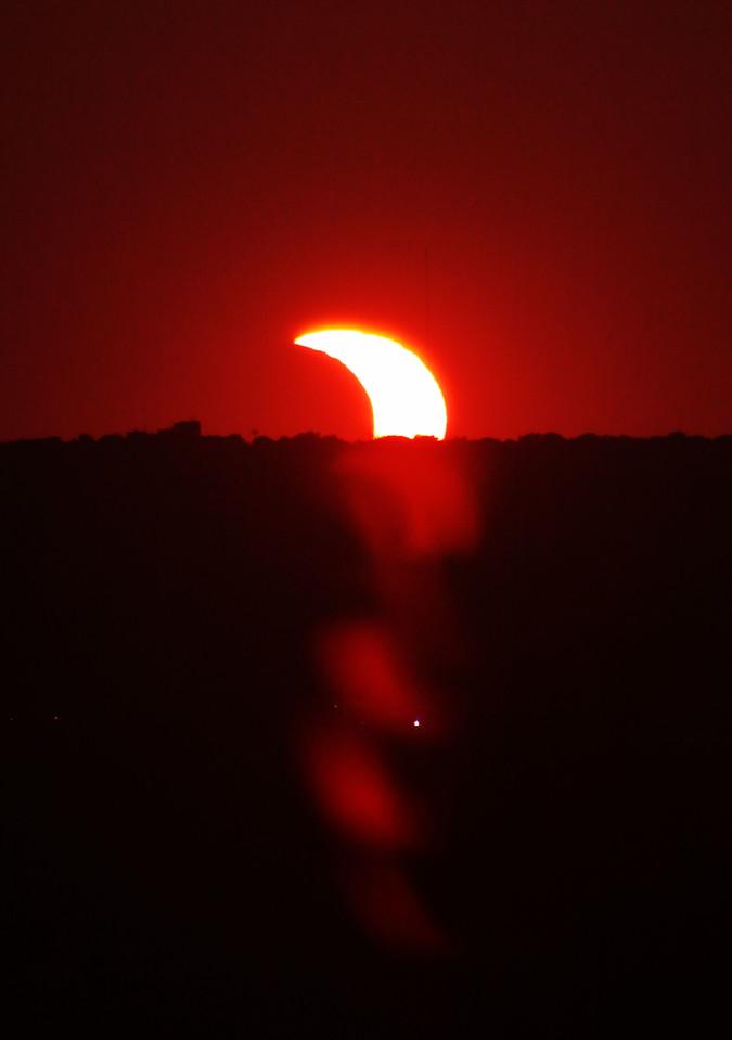 The partial eclipse slipping under the horizon in Omaha, Nebraska.