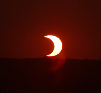 The partial eclipse over the horizon of downtown Omaha, Nebraska.