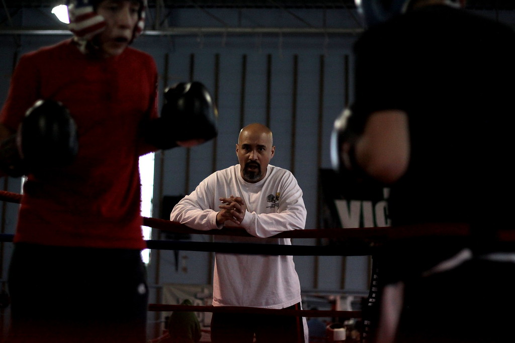 Servando Morales, preacher and coach at Victory Boxing Club in Omaha, looks on as two youth spar in the main ring.