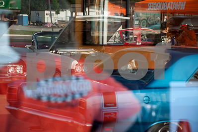 """A parking lot filled with classic cars and car enthusiasts is reflected in the window of Whataburger store 730 in Tyler, Texas Thursday July 9, 2015. This Tyler Whataburger """"Hot Rod Cafe"""" hosts a cruise night car show the second Thursday of each month from March through October. The shows feature cars predating 1976 and each show has a theme such as convertibles, 1950s, Mustangs or Corvettes. This is the 26th year for the Whataburger cruise nights.   (photo by Sarah A. Miller/Tyler Morning Telegraph)"""