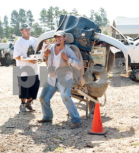 """Ivan Luna of Henderson, Texas loads car parts on his father Juan Luna's back as they prepare to make the 20 foot walk to the checkout at the """"All You Can Carry"""" sale at Locos Gringos Pick-n-Pull in Tyler, Texas Saturday July 25, 2015. Customers starting lining up at 7:30 a.m. to collect self-service auto parts they wanted to buy at the low price of $75 per person. Each person had to carry their items 20 feet on their own to the checkout to utilize the $75 offer.   (photo by Sarah A. Miller/Tyler Morning Telegraph)"""