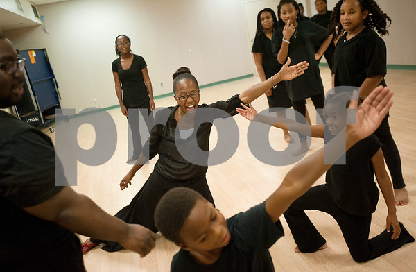 Rashunda Crowder, center, founder of Anointed Hands Studio, smiles with excitement as her youth dancers nail a new dance move during a practice Tuesday at First Baptist Church of Tyler. Anointed Hands Studio is a ministry of the church Higher Dimensions Ministry that teaches praise dance and other forms of dance.  (photo by Sarah A. Miller/Tyler Morning Telegraph)