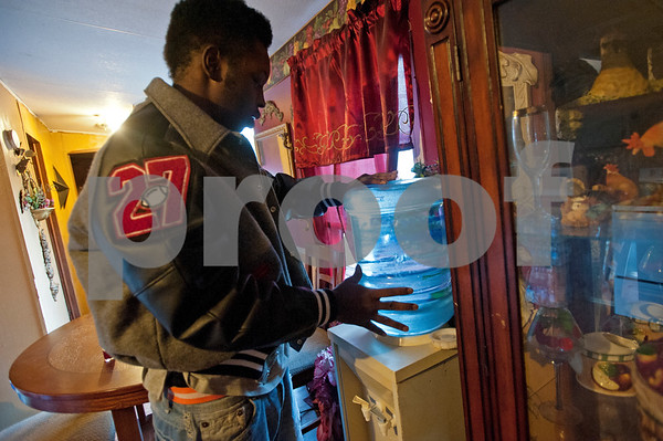 LaTonya Carter's son Tyrell Glenn, 17, puts a donated jug of clean water on a drinking water dispenser in his home Tuesday in the Fairview community outside of Reklaw, Texas Tuesday Jan. 27, 2015. The Carter family is living without running water. A town hall meeting was held at the Reklaw Community Center Tuesday to gauge interest and volunteer participation in applying for a Small Towns Environmental Program grant to pipe water to homes that have never had running water.  (photo by Sarah A. Miller/Tyler Morning Telegraph)