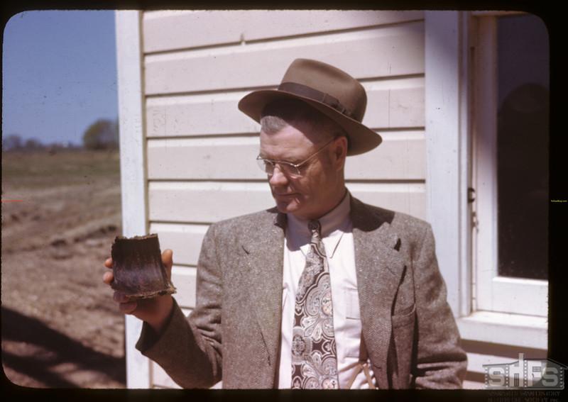 Alex Miller - manager - holding hardened sunflower oil cake. Altona. 05/16/1946