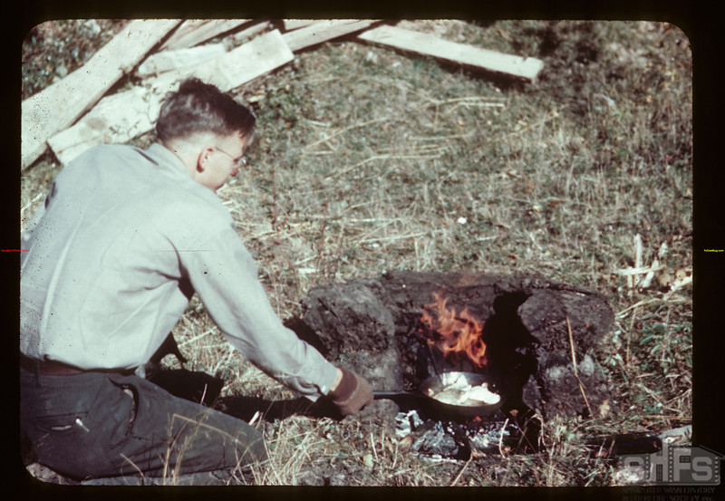Ray Gross of Soil Survey fries fish beside Loon River Compass PO 09/23/1944