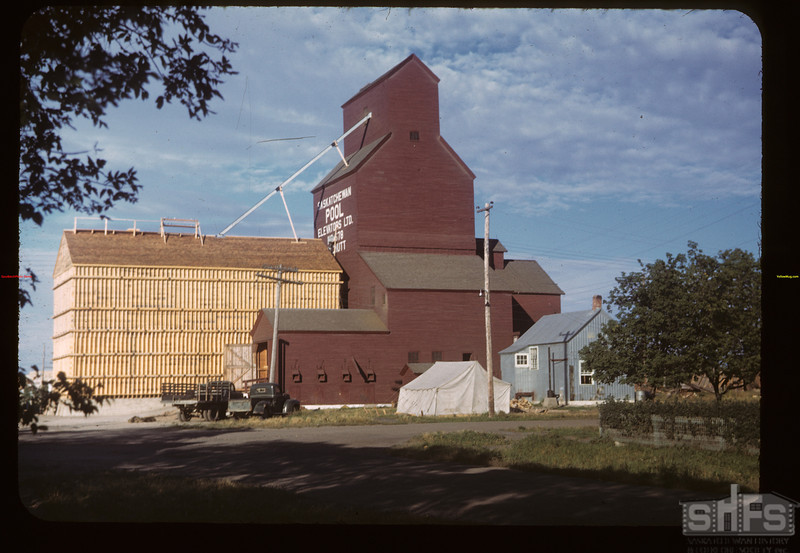 "MacNutt Pool Elevator & new 40 thousand bushel bin. [the braces on the outside of the annex wall are called ""Whalers"" and they hold steel rods that run through the annex to the other side.  These steel rods keep the walls together as the weight of the grain is added into the annex.]	 MacNutt	 09/02/1949"