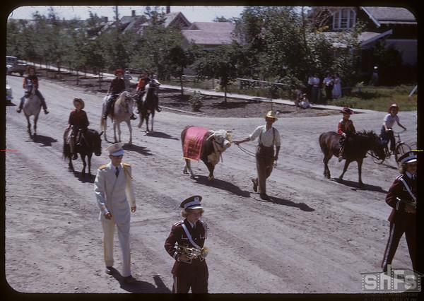 Cowboys and Elmer the bull following band - Shaunavon Fair Parade.  Shaunavon.  07/26/1950