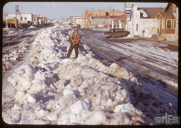 Claude Pickett standing on snow bank on 3rd Ave..  Shaunavon.  03/26/1951