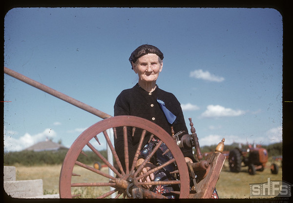 Mrs Norene Wigness at spinning wheel.  Admiral. 08/05/1955