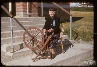 Mrs. Norene Wigness at spinning wheel, Admiral, 08/05/1955