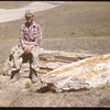 Lyle Bathgate sitting on petrified tree.  South Fork.  08/05/1958