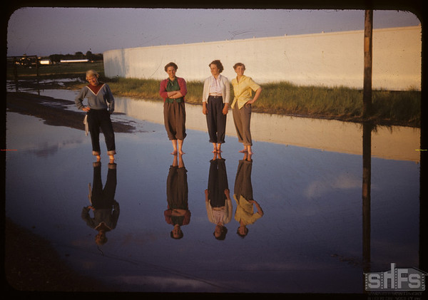 Co-op school girls on the fair grounds after the rain.  Swift Current.  07/09/1954