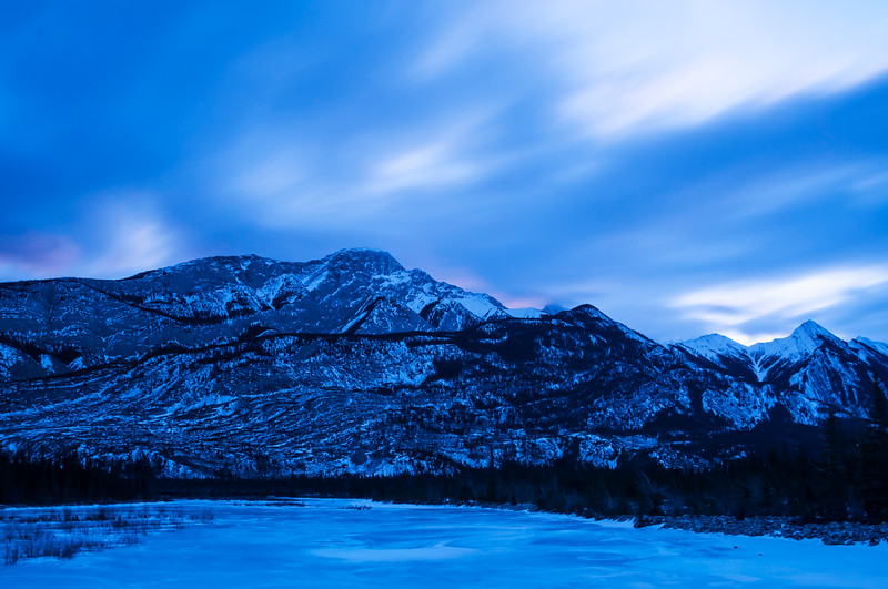 January 23, 2015<br /> <br /> Waiting for the Sunrise<br /> <br /> Snaring River<br /> Jasper National Park, Alberta<br /> <br /> J in J 2015 - When we travel to Jasper we leave in the wee hours of the morning to ensure that we are in the mountain park when the sun comes up. You never know what you will get. There were quite a few clouds so I was hopeful we would get some colour in the sky. In this shot, you can see the pink starting to come through. It turned out to be a truly amazing sunrise!!<br /> <br /> * For the month of January I will, once again, be posting images from my annual trips to Jasper in January.
