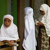 Muslim girls studying outside the village classroom.