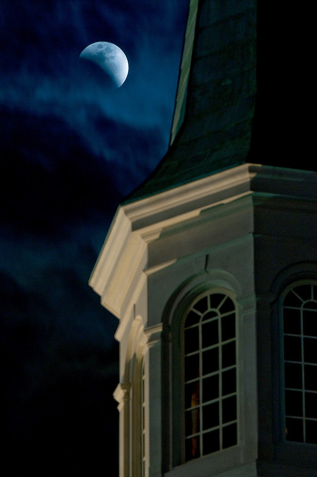The earth's shadow creeps across the moon during the total eclipse on Feb. 20, 2008, as the moon rises alongside the steeple on First Baptist Church in Alexander City, Alabama.