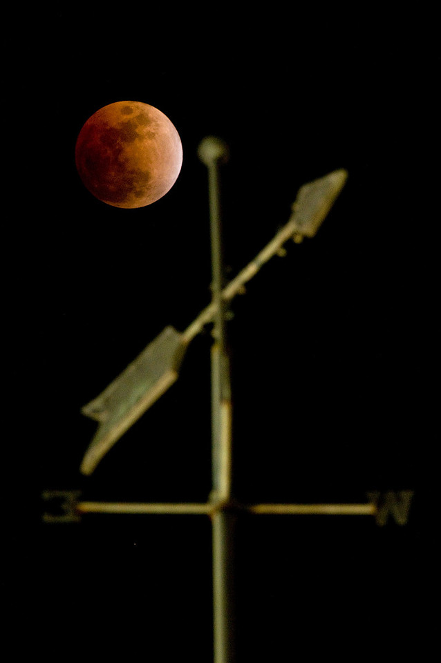 During the middle of a total lunar eclipse, when the moon is completely covered by the earth's shadow, the moon takes on a strange orange glow. This image was taken as the moon rose near a weathervane at the top of the First Baptist Church steeple in Alexander City, Alabama, on Feb. 20, 2008.