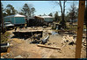 "11Mar08  waveland, ms.  in order to get the mema cabin (the turquoise trailer to the left), the home owner  had to promise to get rid of their existing trailer.  can't have 2 on 1 site. twisted and bent, the original was relocated by katrina.   with only 1 month to get it off site, the homeowner has been dismantling it piece by piece, stacking like components until there was enough to take off and sell as scrap.  this picture was shot from the porch of the new house.  we were tasked w/ taping and mudding the sheet rock, and completing the porch rails.  <a href=""http://carpelumen.smugmug.com/gallery/2530267_2Xcsn/1/135274736_oR39x/Medium"">one year ago.</a>  f/18, 1/200s, iso 200."