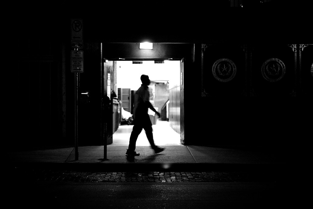 September, 2010<br /> <br /> A valet attendant walks by a restaurant's kitchen entrance one night in downtown Houston.