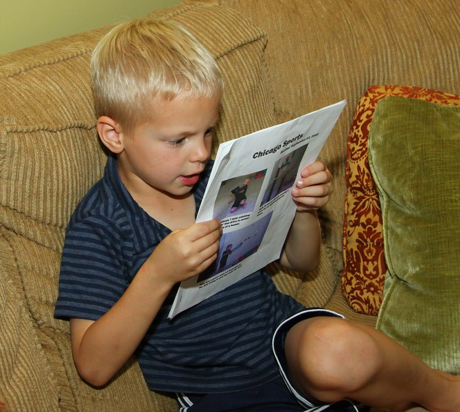 September 13 2010 Reading the sports section<br /> <br /> My six year old grandson Kyle reading his own newspaper. When I got over to his house he told me he wanted me to help him make a newspaper. He already had all the details in his head - 4 pages, what kind of pictures, headlines and copy. We did pictures of him playing baseball, basketball and football. Then we got on the computer and he showed me which pictures he wanted, where he wanted them on each page, how big to make them, etc. Then he dictated the captions for each picture using names of real sports teams and players.  He was quite precise about fonts and font sizes. On the back page we created box scores and summaries.  He was thrilled with the result.  And, I couldn't have had more fun.